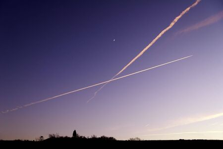 evening horizon with silhouette and crossing condensation trails on sky Stock Photo - 4830672