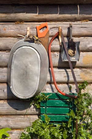 besom: tool kit on wooden lodge wall
