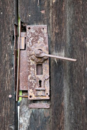 antique keyhole: old rusty door lock on an ailing wooden gate Stock Photo