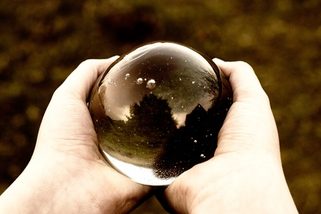 witchery: round magical crystal ball with reflections in the hands Stock Photo