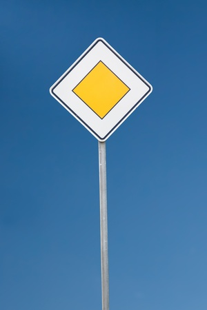 give way: a give way sign against blue sky Stock Photo