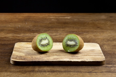 actinidia deliciosa: sliced kiwifruit on a wooden board