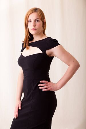madam: Woman with red hair and black dress Stock Photo