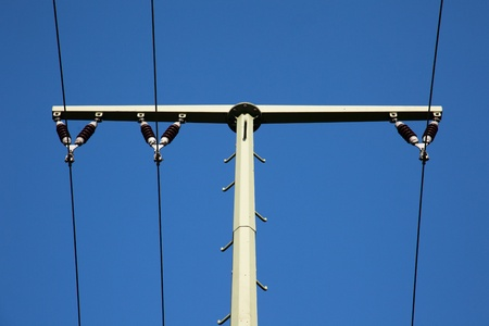 overhead line span pole in front of blue sky photo