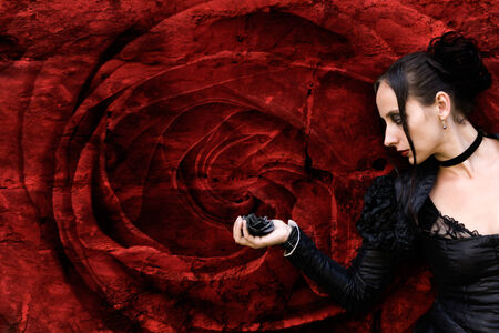 black Woman with black rose in front of a red rose blossom