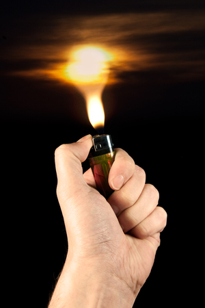 The fire of a lighter with a sunset fades Stock Photo - 25313225