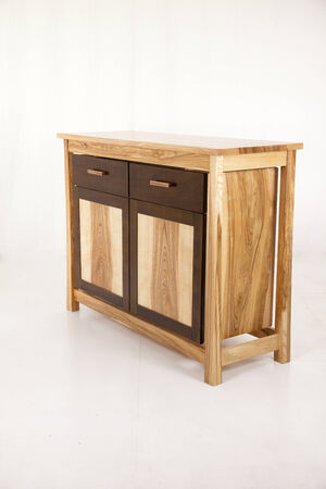 An elegant chest of drawers made   8203;  8203;of pine wood in front of gray background photo