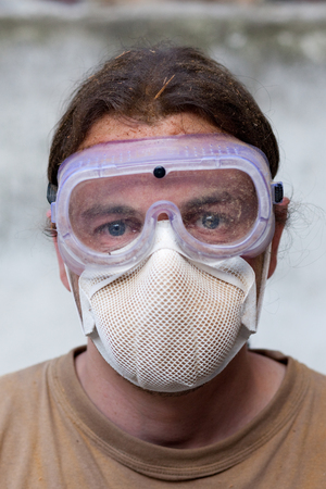 Worker with breathing mask and wood shavings in the hair photo
