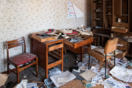devastated: an abandoned office with scattered documents Editorial