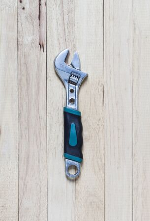 tighten: wrenche on wooden background