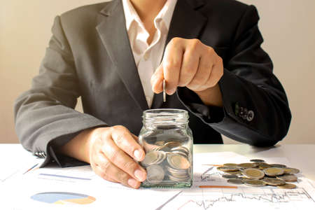 Business woman holding a coin in a money jar and window light money saving idea.
