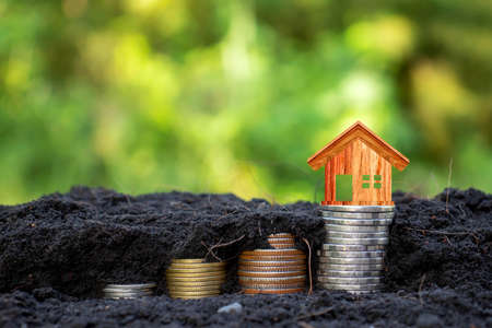 Wooden house model on coin contains coins growing in the ground with money saving concept, green nature background.