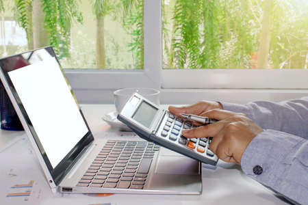 Close-up of a woman pressing the calculator to calculate expenses, calculation concepts, and saving money for the future.
