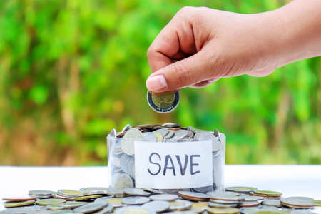 Hand holding a coin in a piggy bank on a natural green background, concept to grow and save money.