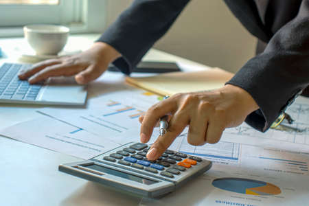 Male accountants are working on financial documents and calculators for business and finance expenses.