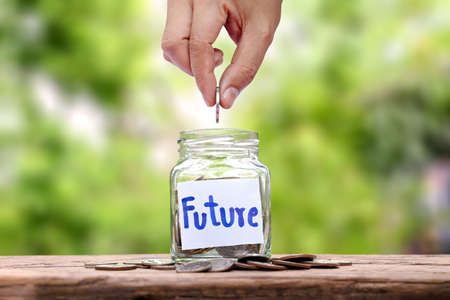 Hand-holding coin in a jar for saving money on wood floor financial concept Business and investment stocks grow high. Zdjęcie Seryjne