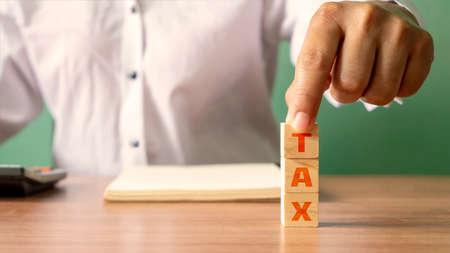 Young woman holding a wooden cube with the word Tax, financial concept. Financial Management and Tax Planning
