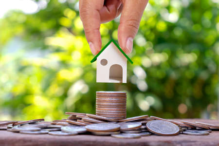Hand holding mock house on a pile of coins with blurred green nature background, home loan and real estate investment loan.
