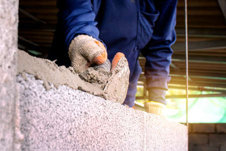 Close-up of a professional worker using a pan knife to build a brick wall with cement bricks and cement. Business ideas and the construction industry Zdjęcie Seryjne