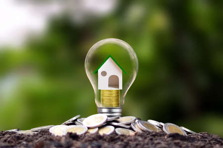 Model houses are on piles of coins in energy-saving lamps. energy saving concept Renewable energy and real estate investment loans