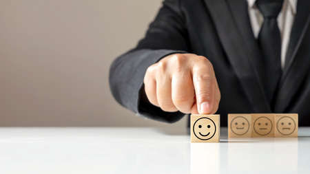 Hand holding Happy icon on a wooden cube block on the table, business annual satisfaction survey concept.