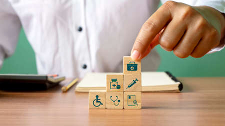 Close-up of human hand stacking wooden blocks overlapping health care icons and medical icons. The concept of choosing health insurance rights when sick