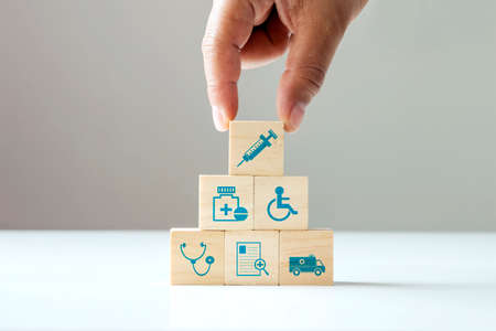 Stacking wooden blocks, human hand health care icons and medical icons. The concept of choosing health insurance rights when sick Zdjęcie Seryjne