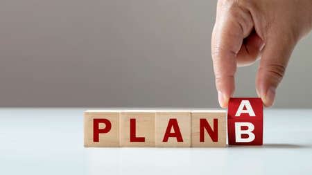 Businessman's hand flips wooden cube blocks from Plan A to Plan B. SME organization solution ideas and business solutions.