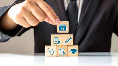 The medical icon on wooden cube block and male businessman hand choosing medicine bag icon on wooden cube block, good health care, and insurance concept.