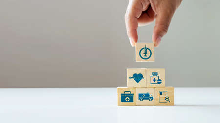 business hand-select on-off icon on wooden cube block and medical icon good health care and insurance concept