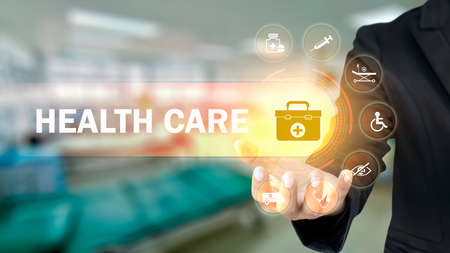 Businessman holding icons with medical symbols on blurry background, health insurance concept. Health care and health insurance business