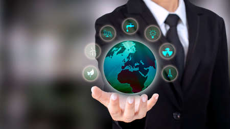 Energy Business Investment Ideas environmentally friendly clean energy icon and the globe in the hand of a businessman wearing a suit