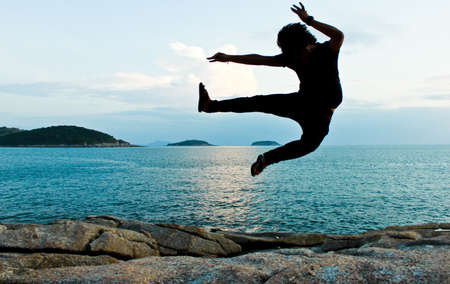 a jumping man with sea background silhouette photo