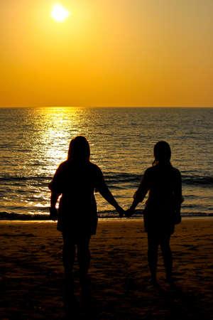 silhouette sunset beach handing photo