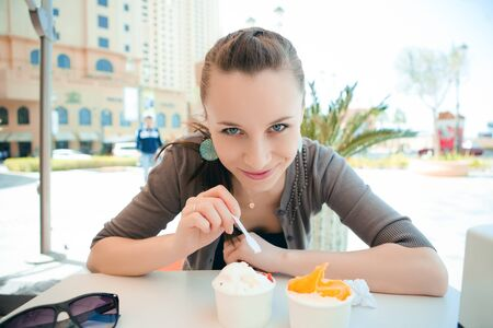 Young beautiful woman eating ice cream outdoor