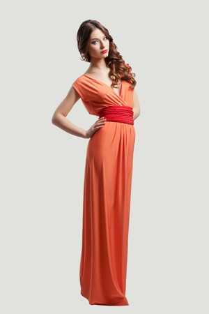 Model with beautiful long hair posing in orange dress isolated photo