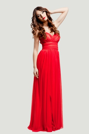 Beautiful female fashion model posing in red dress in studio photo