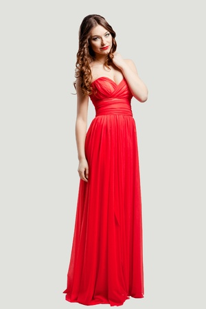 Beautiful female fashion model posing in red dress in studio Stock Photo