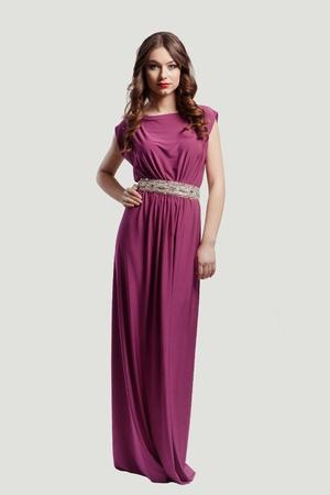 Beautiful female fashion model posing in purple dress photo