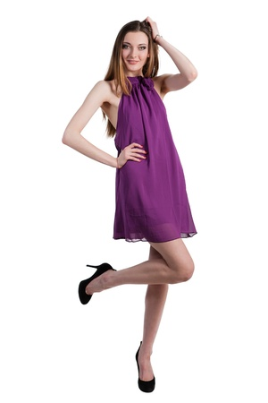Beautiful female fashion model posing in purple dress