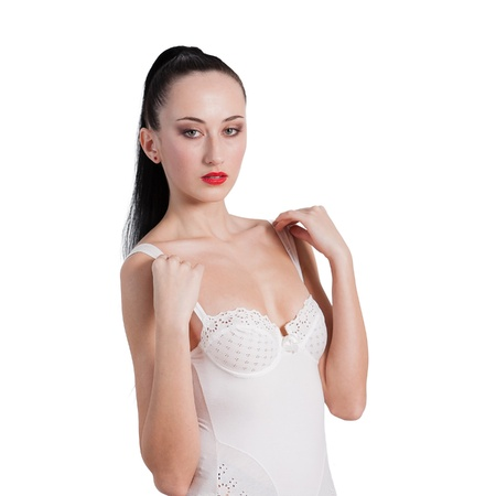 Portrait of young lady standing in lingerie against white background Stock Photo