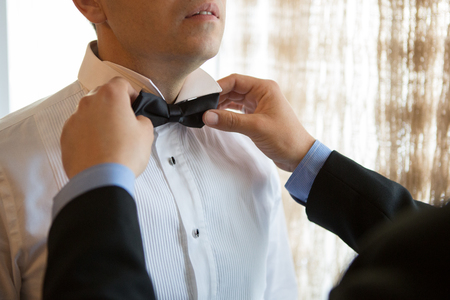 corrects: Man corrects his friend bow tie