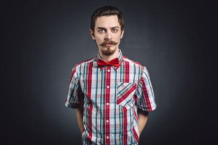 Man in plaid shirt and bow tie in the studio