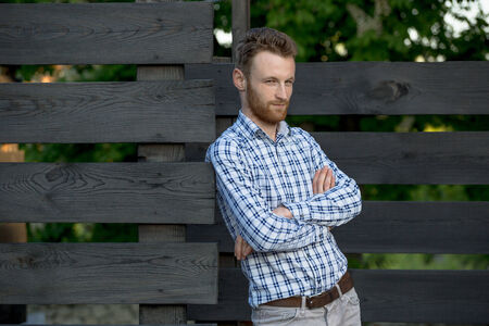 Portrait of young fashionable man against wooden fence Stock Photo