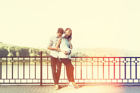 Happy and young pregnant couple hugging in nature at the lake. Vintage retro style with light leaks
