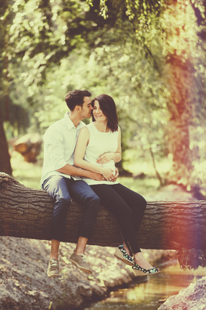 Happy and young pregnant couple hugging in nature. Vintage retro style with light leaks