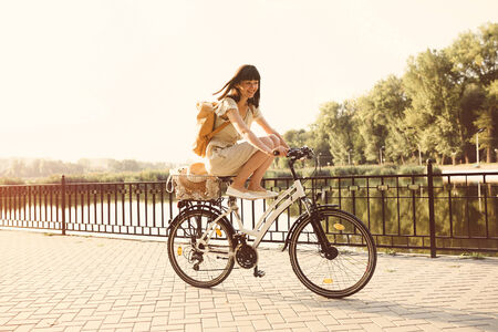 Girl riding a bicycle in park near the lake.  photo