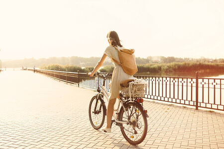 bicycle girl: Girl riding a bicycle in park near the lake.  Stock Photo