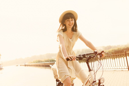 Girl riding a bicycle in park near the lake.  Stock Photo