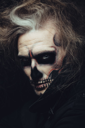 horror face: Portrait of man with Halloween skull makeup Stock Photo